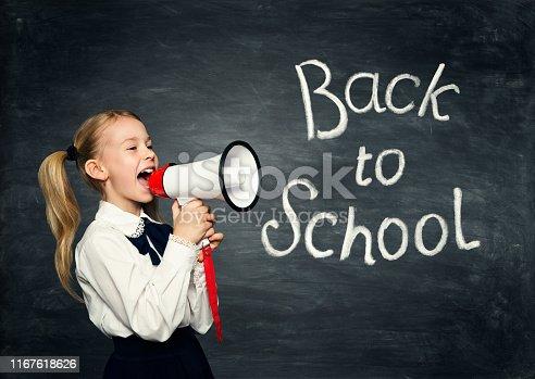 991060890 istock photo Child Girl Screaming In Megaphone, Back to School Advertisement, Pupil Kid Advertising over Blackboard 1167618626
