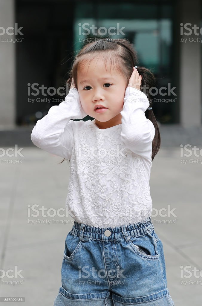 Child girl shutting down her ears, holding her hands covers ears not to hear. stock photo