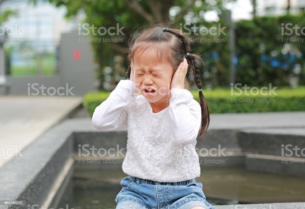 Child girl shutting down her ears, holding her hands to cover ears not to hear. stock photo