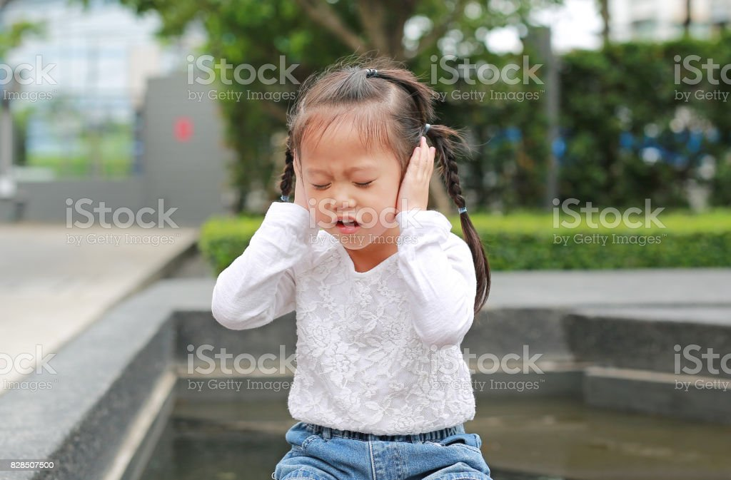 Child girl shutting down her ears with smiling. stock photo