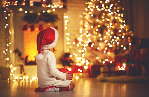 868220646 istock photo child girl  sitting  back in front of  Christmas tree on Christmas Eve 868220646