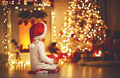 istock child girl  sitting  back in front of  Christmas tree on Christmas Eve 868220646