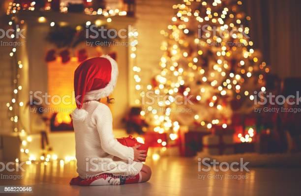 Child girl sitting back in front of christmas tree on christmas eve picture id868220646?b=1&k=6&m=868220646&s=612x612&h=ewrxxncx8hdkghr9nsmiryjg8eio4zfdg1ymfvcrtmq=