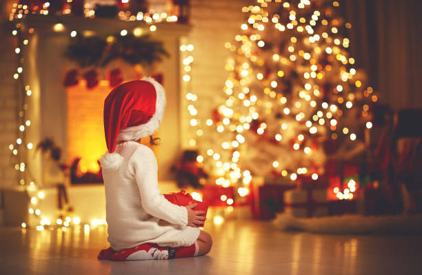 child girl  sitting  back in front of  christmas tree on christmas eve - christmas families stock photos and pictures