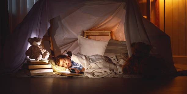 child girl sleeping in tent with  book and flashlight - foto de stock
