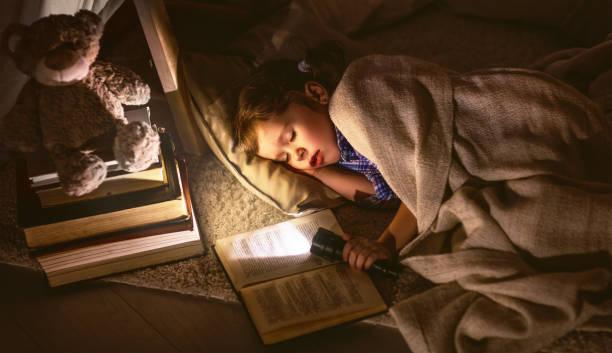 child girl sleeping in tent with  book and flashlight - tipi bett stock-fotos und bilder