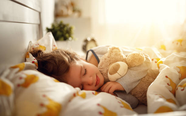 child  girl sleeps in her bed with toy teddy bear  in morning child  girl sleeps in her bed with a toy teddy bear  in morning bedtime stock pictures, royalty-free photos & images