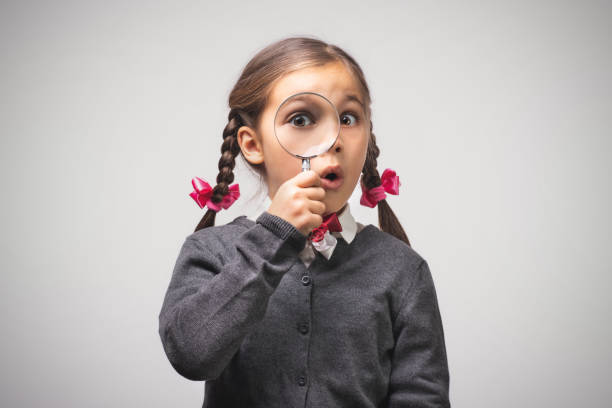 Child Girl Student Looking Through Magnifying Glass on Grey Background with Available Copy Space. Back to School Concept. stock photo