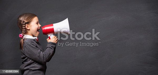 991060890 istock photo Child Girl Student Shouting Through Megaphone on Blackboard Back 1165880384