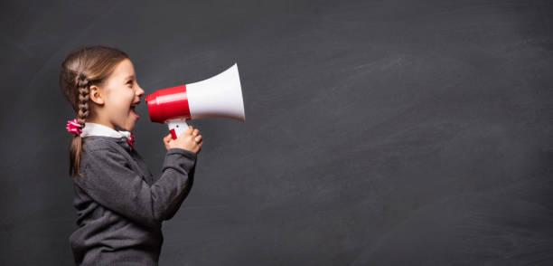 Kind Mädchen Student schreien durch Megaphon auf Tafel zurück – Foto