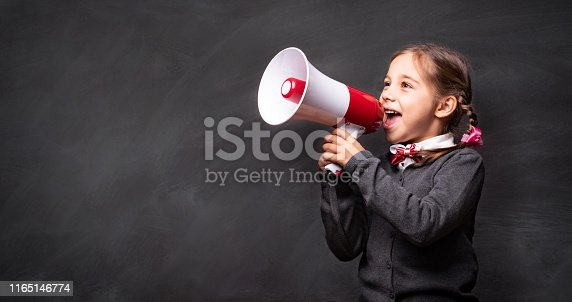 991060890 istock photo Child Girl Student Shouting Through Megaphone on Blackboard Backdrop with Available Copy Space. Back to School Concept. 1165146774
