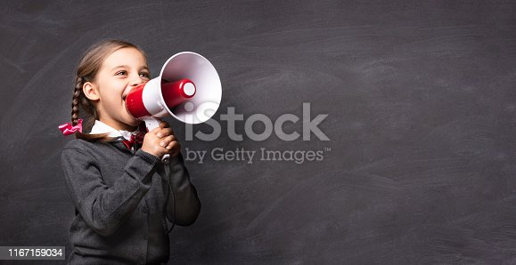 991060890 istock photo Child Girl Student Shouting Through Megaphone on Blackboard Backdrop with Available Copy Space. Back to School Concept. 1167159034