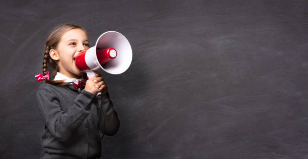 Child Girl Student Shouting Through Megaphone on Blackboard Backdrop with Available Copy Space. Back to School Concept. stock photo