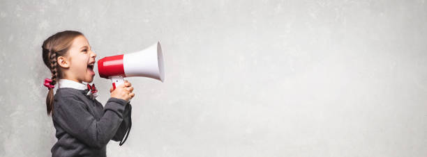 Child Girl Student Shouting Through Megaphone on Grey Backdrop with Available Copy Space. Back to School Concept. stock photo