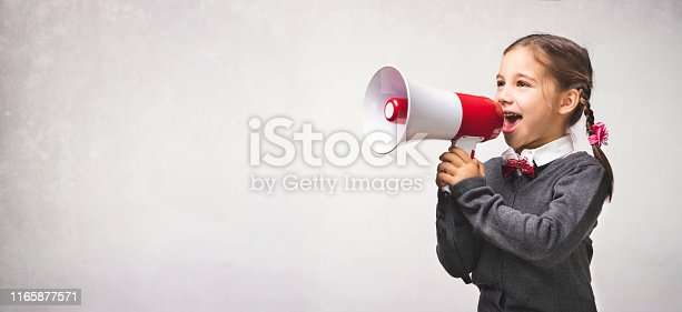 991060890 istock photo Child Girl Student Shouting Through Megaphone on Grey Backdrop with Available Copy Space. Back to School Concept. 1165877571