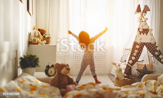 istock child girl wakes up  and stretches in morning in bed and stretches 924465368