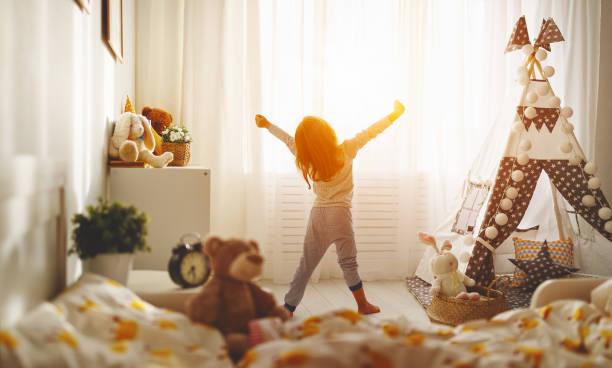 menina criança acorda e estende-se na cama de manhã e se estende - foto de acervo