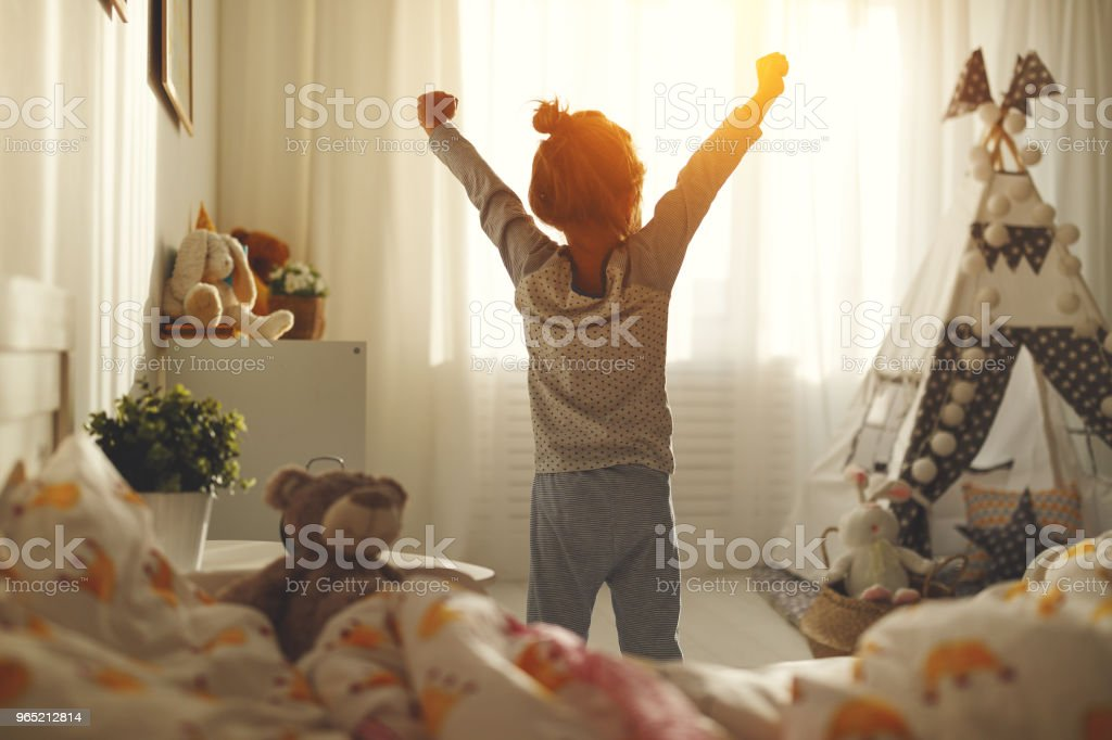 child girl wakes up  and stretches in morning in bed and stretches zbiór zdjęć royalty-free