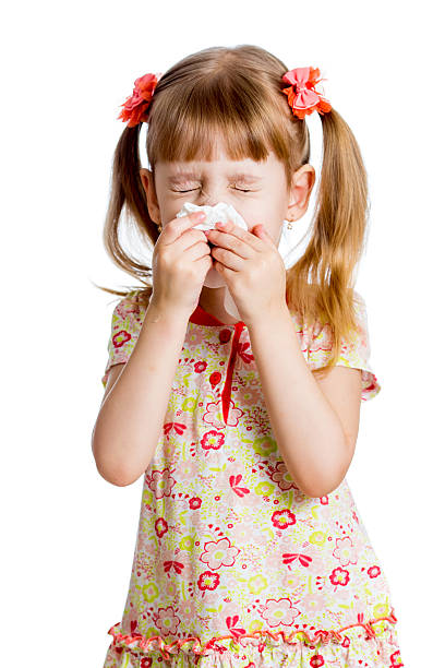 child girl wiping or cleaning nose with tissue isolated stock photo