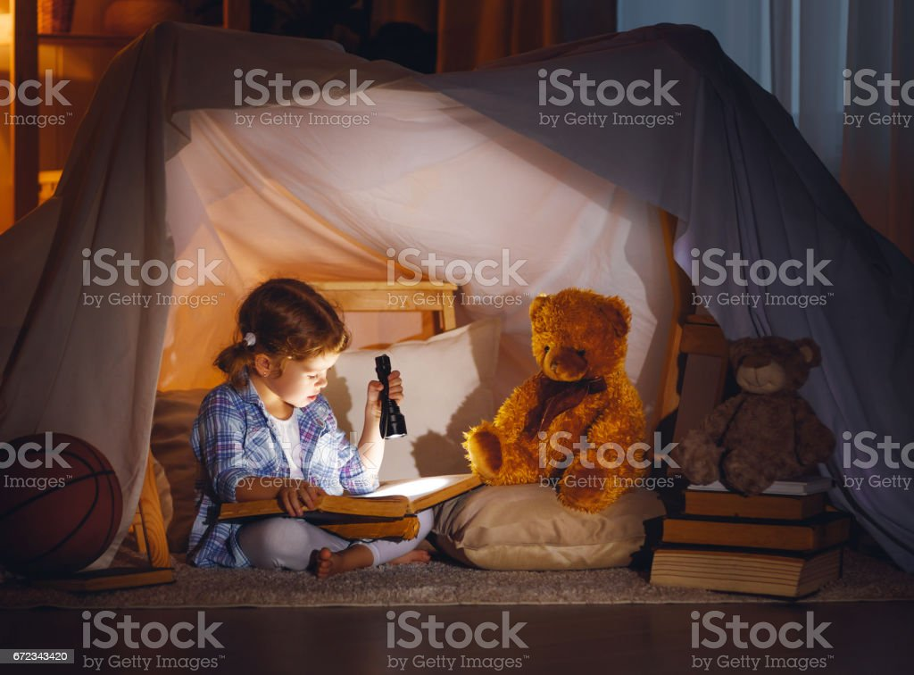 child girl with a book and a flashlight and teddy bear before going to bed stock photo
