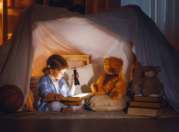 child girl with a book and a flashlight and teddy bear before going to bed - foto de stock