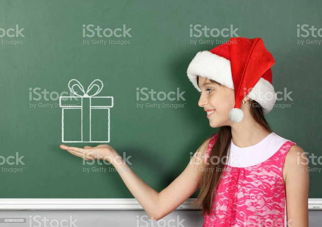 child girl with santa hat hold drawn gift box near school blackboard stock photo