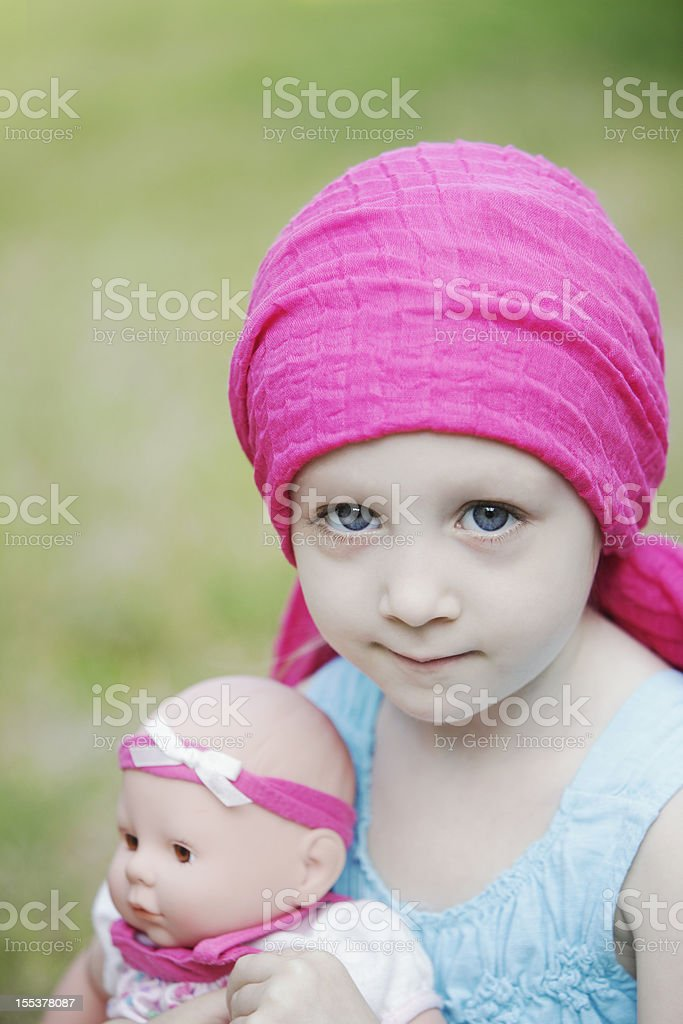 Child girl with scarf on her head holding a doll royalty-free stock photo