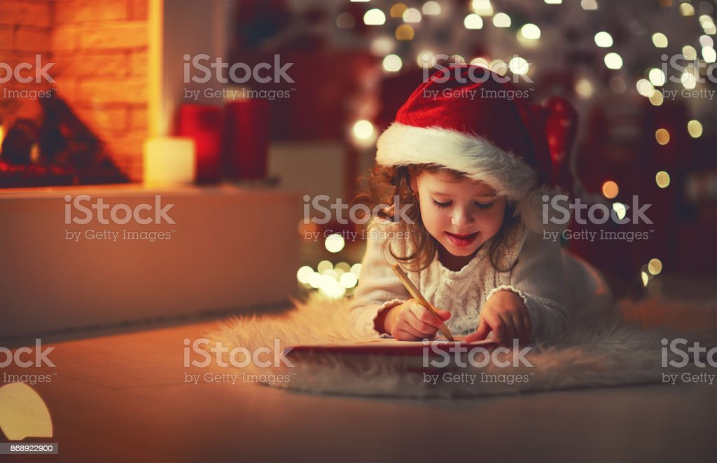 child girl writing letter santa home near Christmas tree - foto stock