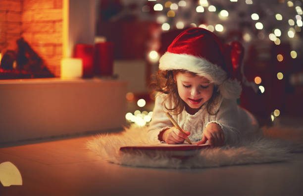 child girl writing letter santa home near christmas tree - note message stock photos and pictures
