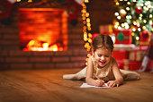 istock child girl writing letter santa home near Christmas tree 870899054