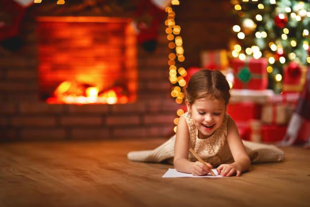 kind mädchen schreiben brief santa hauptnahem weihnachtsbaum - weihnachts wunschliste stock-fotos und bilder