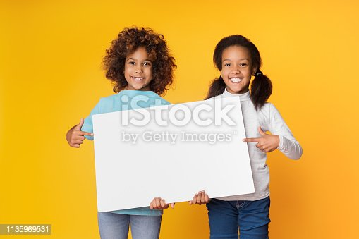 Child girls holding empty banner and pointing on it, copy space, yellow background