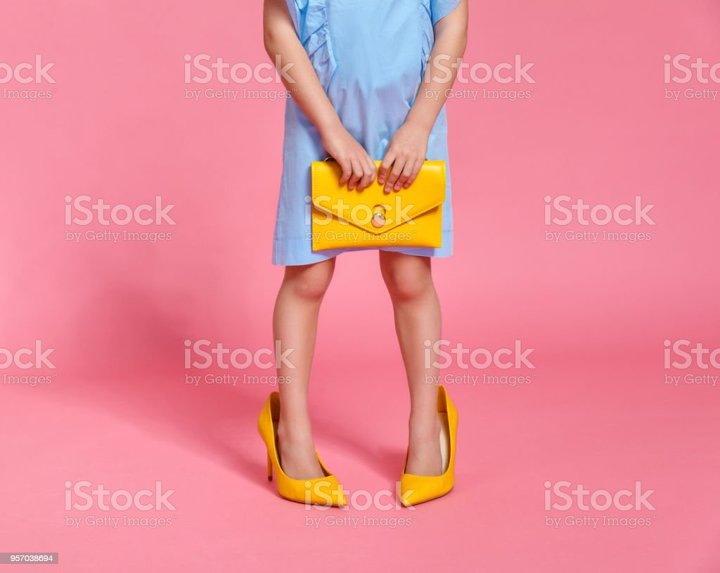 child girl's legs in large high heeled shoes on colored background - foto stock