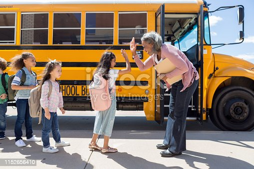 While waiting in line to board the school bus, a young female student gives the bus driver a high-five.