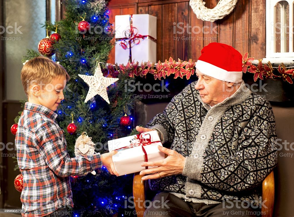 Child giving a gift to Grandpa stock photo
