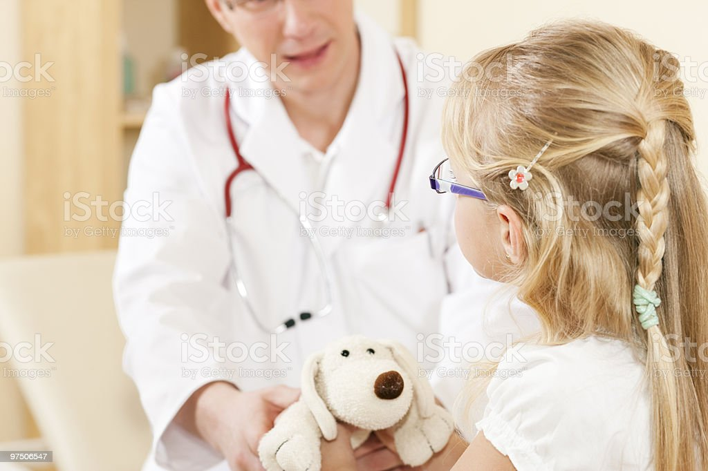 Child giving a soft toy to doctor royalty-free stock photo