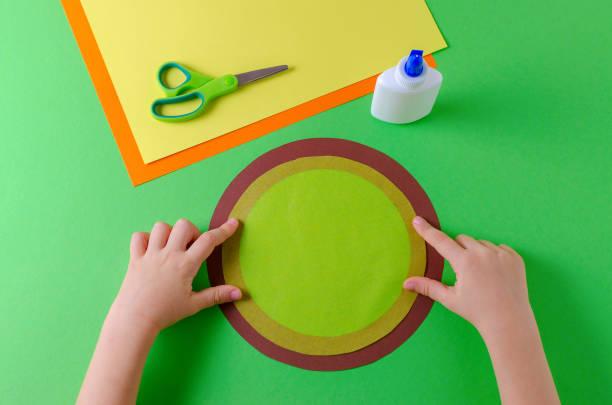 kind klebt zwei kreise mit farbenpapier, klebstoff und schere - diy eule stock-fotos und bilder