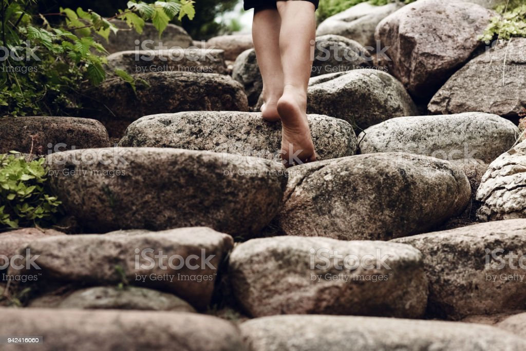 Child goes up the stairs in the garden in the summer stock photo