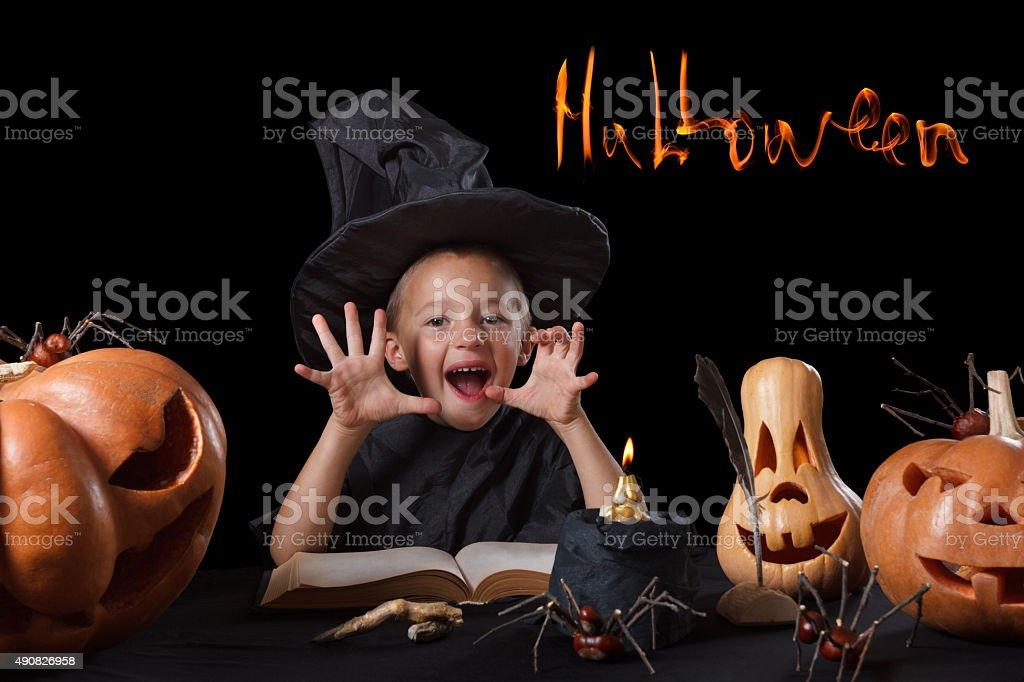 Child, Halloween pumpkin, magical things  on black background stock photo