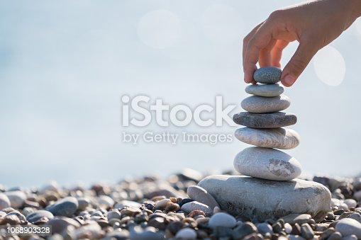 Child Hand balancing stack of stones on beach