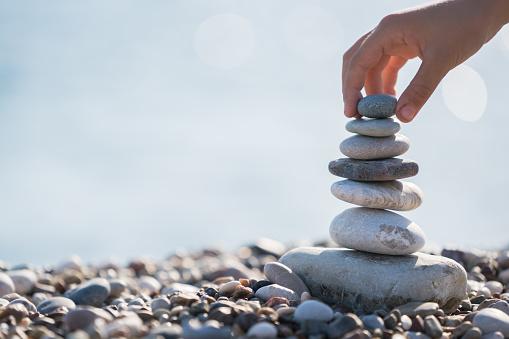 Child Hand balancing stack of stones on beach
