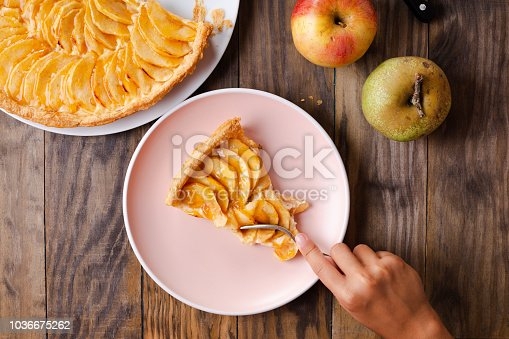 Little girl hands eating a portion of apple pie tart on a pink dish on rustic wooden background. Top view