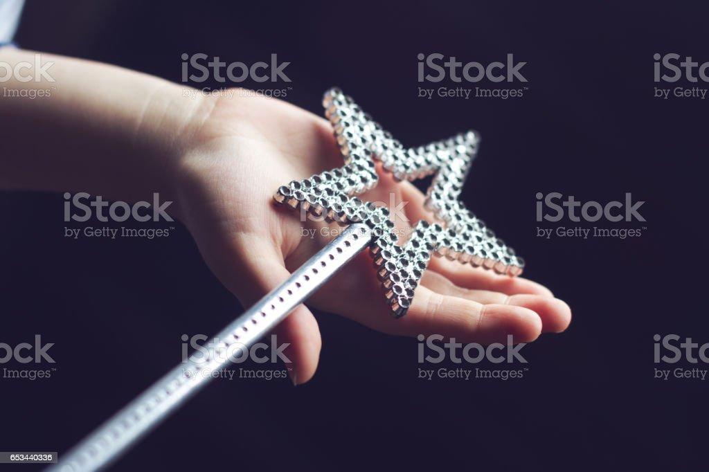 main d'enfant tenant une baguette magique - Photo