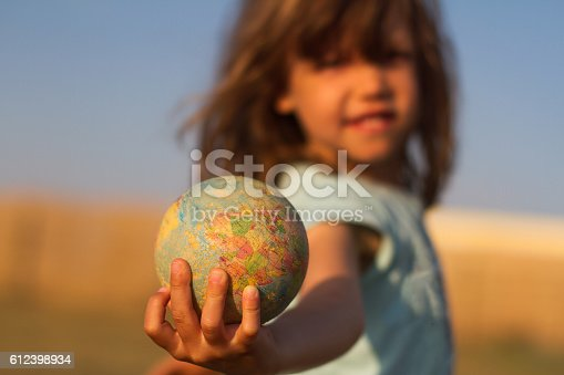 istock Child hand holding an earth toy globe 612398934