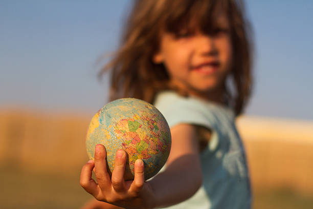 child hand holding an earth toy globe - globus reisen stock-fotos und bilder