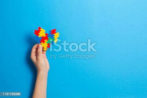 istock Child hand holding colorful heart on blue background. World autism awareness day concept 1131155395