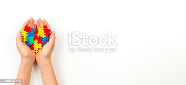istock Child hand holding colorful heart on white background. World autism awareness day concept 1138232609