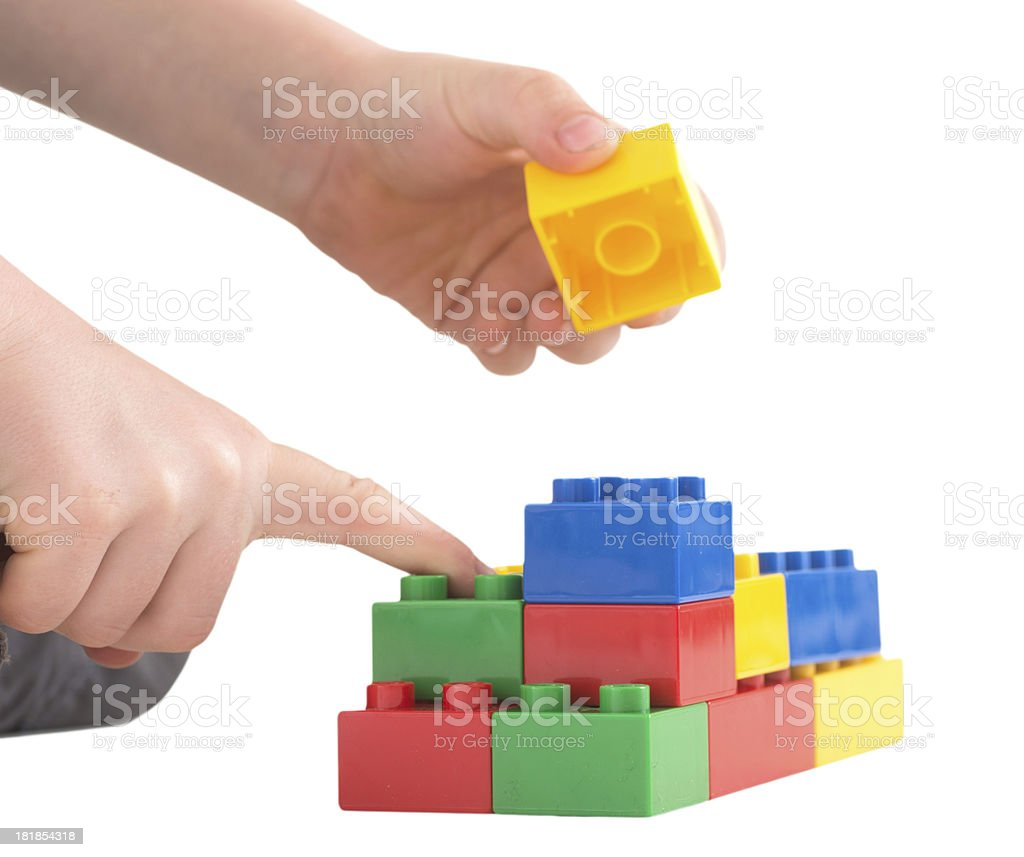 child hand is building with colored toy bricks stock photo