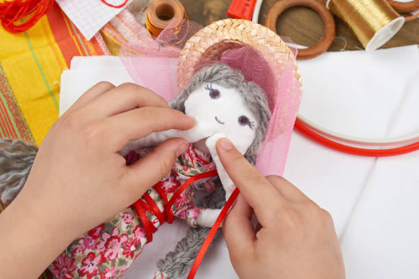 child hand making dress for handmade doll, learn to sewing - nähpuppen stock-fotos und bilder