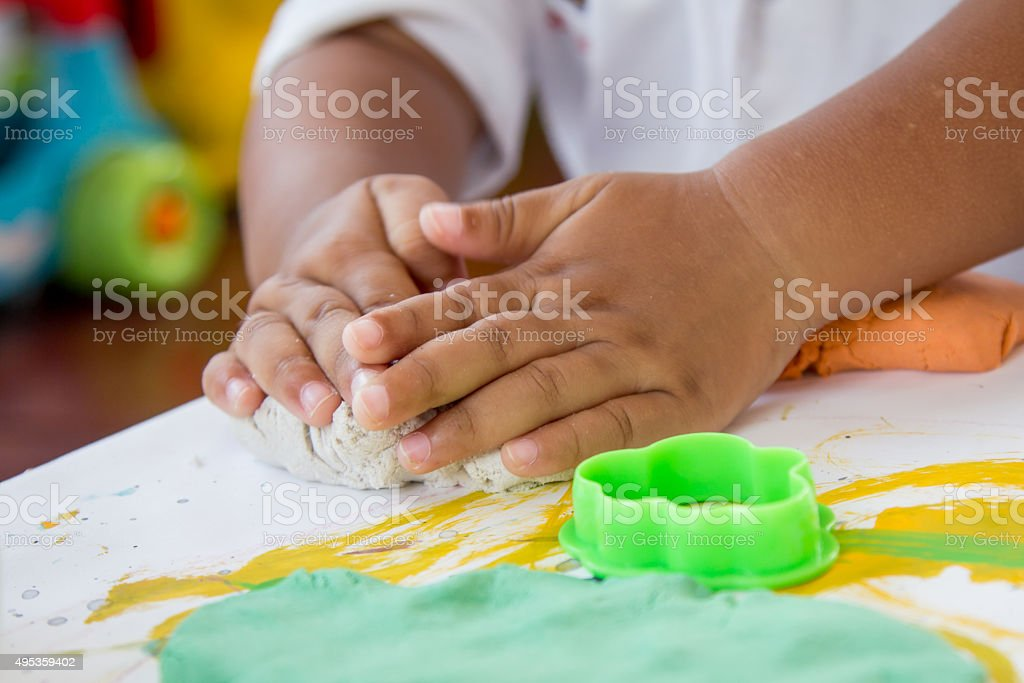 Child hand playing with clay, play doh stock photo